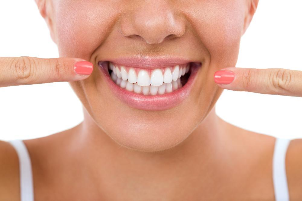Woman smiling & pointing at teeth | Cosmetic Dentist Seattle WA