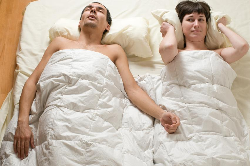 Woman laying in bed awake because partner is snoring